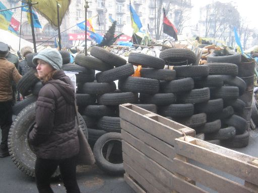 A barricade of tires and shipping planks, with both the official and alternative Ukrainian flags overhead