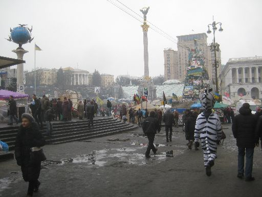 Another view of the main protest area with booths, flags, Euromaidan 'Christmas tree,' and person in zebra costume.