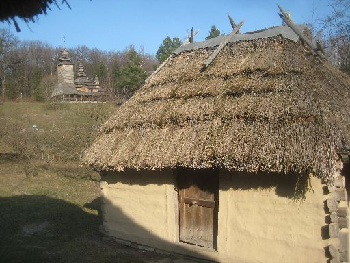 A hut with the Church of Kanora village (1792) in the background, Transcarpathian region