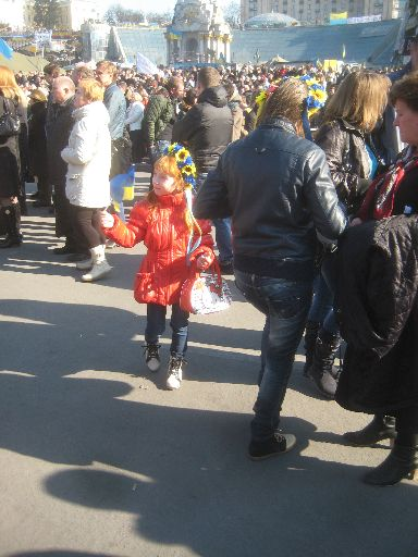 A girl on the Maidan with Euromaidan (and Hello Kitty) paraphernalia, the Independence Monument behind her