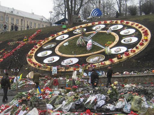 The memorials on, in front of, and beside the clock on Instytutska Street.  Many flower arrangements are in the colors of the Ukrainian flag, and one in the center is in the design of the flag of Georgia, the country Russia last invaded before invading Crimea.